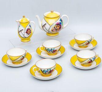 Чайник, молочник и пять чайных пар из сервиза с эмблемами и цветами на желтом фоне